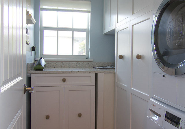 laundry room with white cabinets and stacked washer and dryer